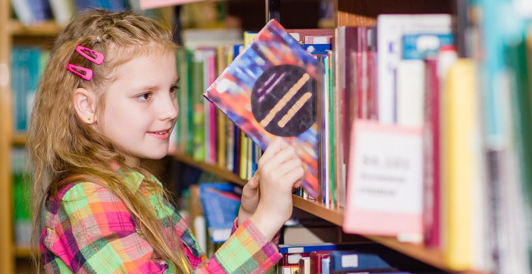 Jeune fille qui choisit un livre en Français dans la bibliothèque de l'école